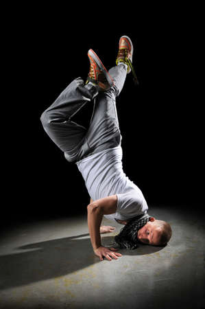 Young breakdancer performing free-style dancing over dark background