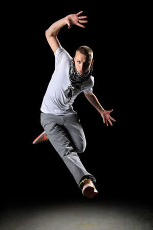 Hip hop dancer jumping over a dark background 版權商用圖片