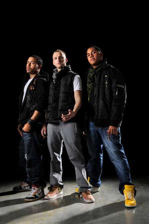 raperos: Bailarines de hip-hop posando sobre un fondo oscuro