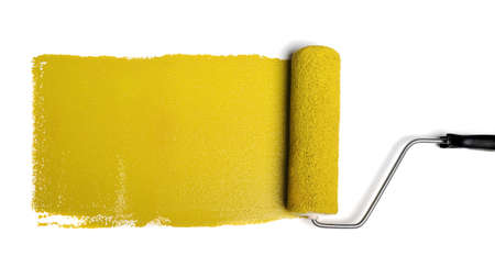 roller: Paint roller leaving stroke of yellow paint over a white background