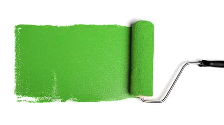 白い背景の上の緑のペンキのストローク ペイント ローラー