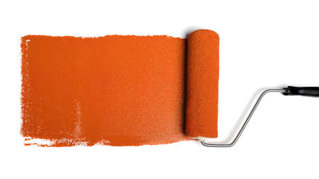 Paint roller leaving stroke of orange paint over a white background photo