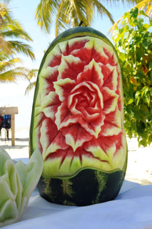 Carved watermelon on a table over tropical background