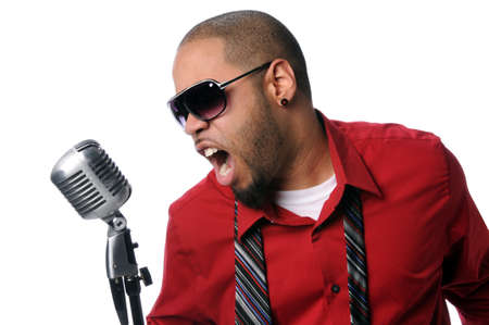 Young African American man singing into vintage microphone isolated over white photo