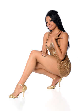 Young African Americna woman dressed in golden dress with high heels Stock Photo