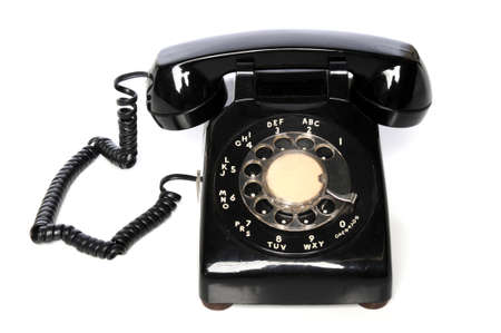 Vintage black telephone over a white background photo