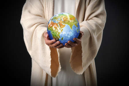 イエスが黒っぽい背景に彼の手で世界を保持