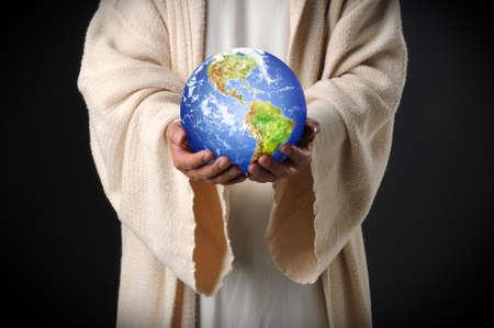De handen van de holdingswereld van Jesus overhandigen binnen donkere achtergrond Stockfoto