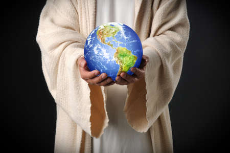 Hands of Jesus holding world in hands over dark background photo