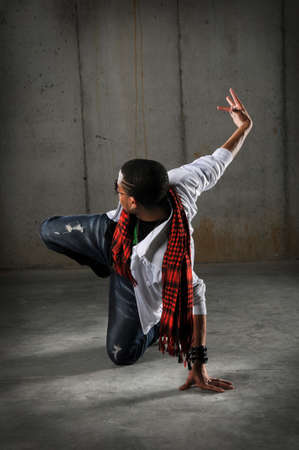 African American hip hop dancer performing over grunge background photo