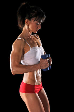 female bodybuilder: Mature woman curling dumbbells isolated over a black background