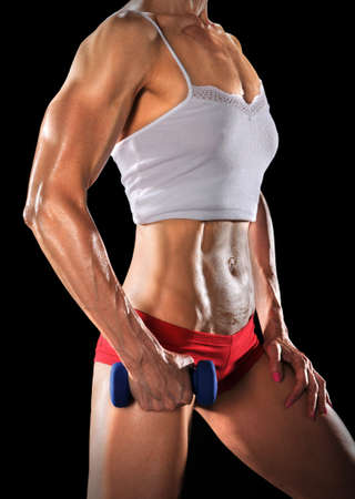 female bodybuilder: Mid section of fit woman holding dumbell isolated over black background