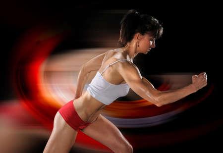 toned: Female athlete running isolated over black background Stock Photo