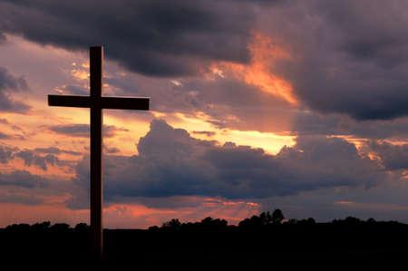 Houten kruis over een zonsondergang