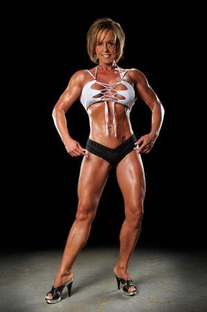aged: Female bodybuilder posing over a dark background