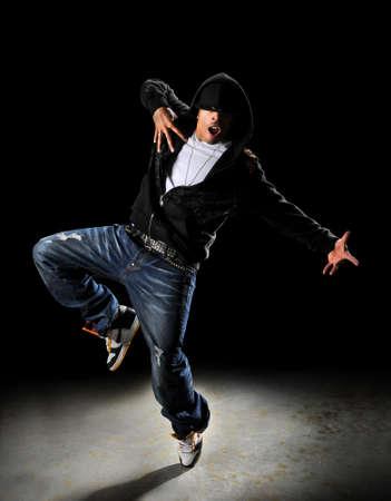 スポット ライトで暗い背景の上にフード付きのヒップホップ スタイルのダンサー