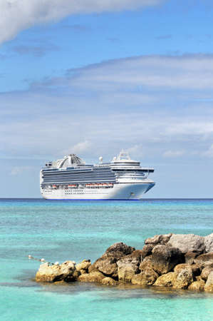 cruises: Cruise ship anchored in tropical waters with rocks in foreground Stock Photo
