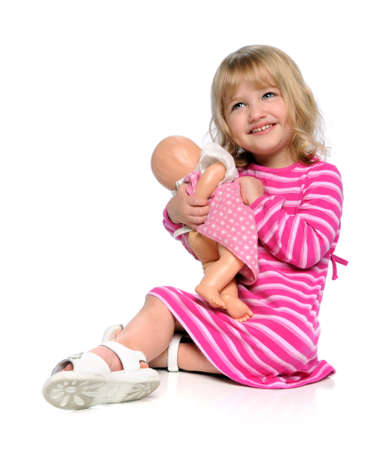 Young girl playing with doll isolated over white photo