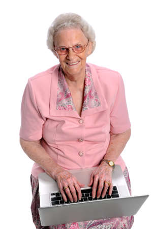aging woman: Portrait of elderly woman typing on laptop over white background Stock Photo