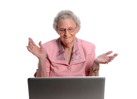 Senior woman throwing hands in front of laptop computer isolated over white