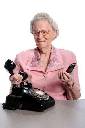 Elderly woman holding vintage phone and cellphone isolated over white background photo