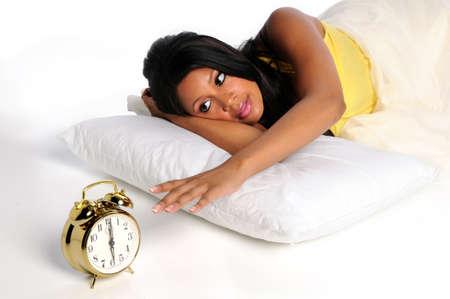 woman clock: Mujer afroamericana despertarse extendiendo la mano del reloj de alarma  Foto de archivo