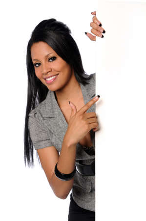 African American businesswoman smiling and pointing to blank sign Reklamní fotografie