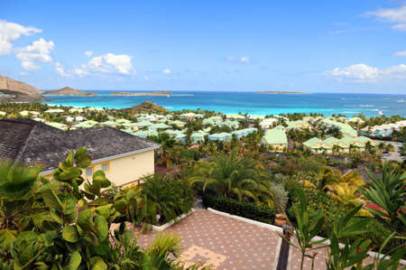 View of house in Saint Martin with rooftops and beach in background photo