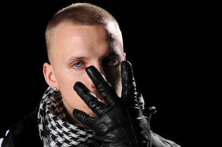 Portrait of hip hop man with gloved hand in front of face photo