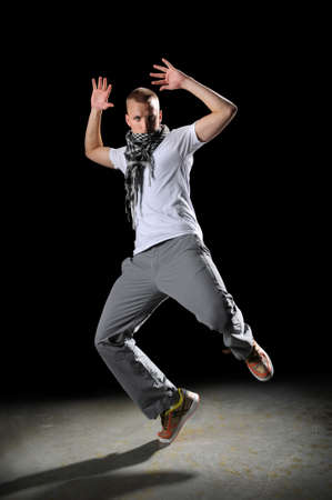 Portrait of hip hop young man dancing over dark background photo