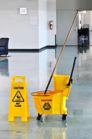 Mop bucket and caution sign on a web floor photo