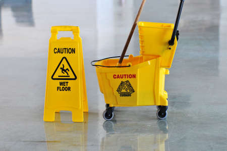 Mop bucket and caution sign on wet floor photo