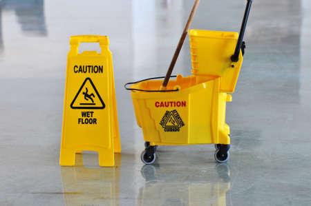 achtung schild: MOP-Eimer und Vorsicht unterzeichnen auf nassen Boden