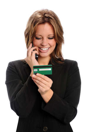 business cards: Woman using credit card while talking on cell phone isolated over white background