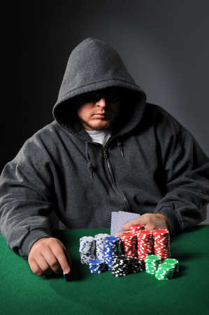 Poker player holding chip staring through sunglasses