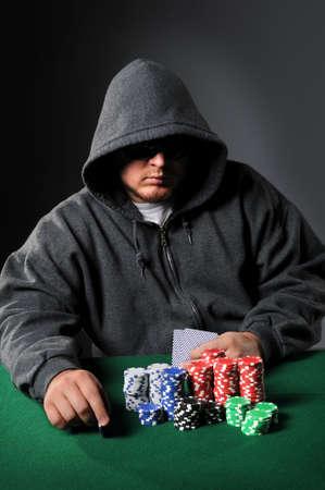 Poker player holding chip staring through sunglasses