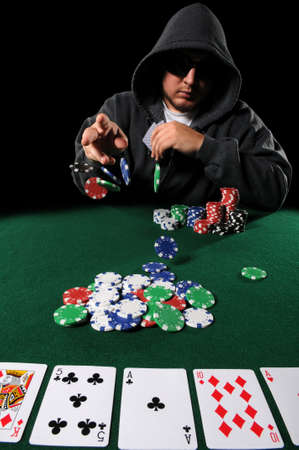 Poker played with hood and sunglasses throwing chips on stack