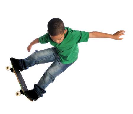 ni�o en patines: Chico de j�venes afroamericanos realizar truco con placa de skate aislado sobre blanco