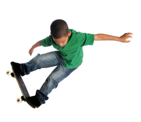 skateboarding: Young African American boy performing trick with skate board isolated over white