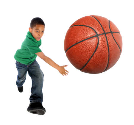 boy skating: Young African American boy playing basketball - Selective focus on ball Stock Photo