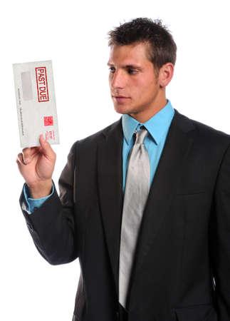 Businessman holding past due envelope isolated over white background photo