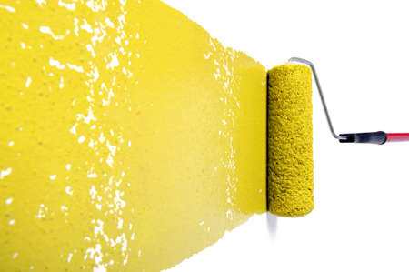 Pain roller with yellow paint on white wall photo