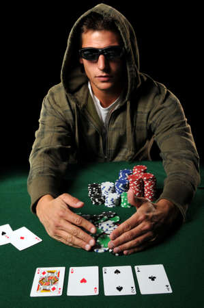 Poker player with sunglasses gathering winning chips Editorial