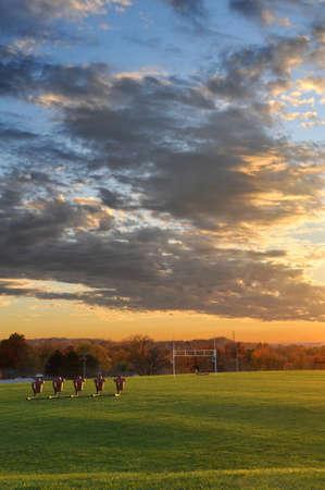 football goal post: Football field at sunset during fall season