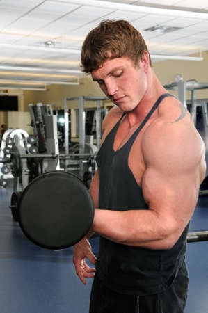 Man working out at gym curling a dumbbell photo