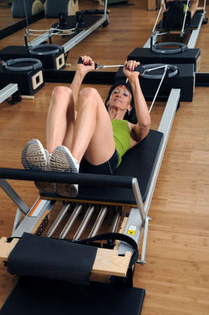 Woman Practicing Pilates work our at gym photo