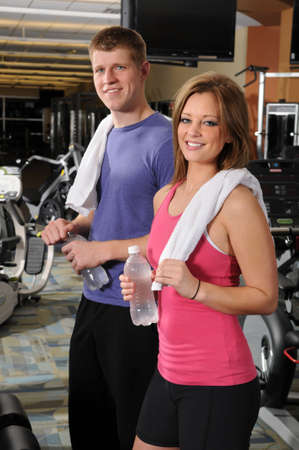 Man and woman holding botled water at the gym