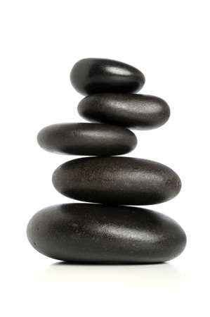 zen stones: Five black stones balanced isolated over white background