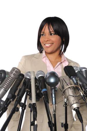 hablar en publico: Mujer afroamericana hablando en delante de los micr�fonos m�ltiples