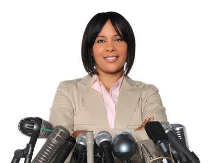 hablar en publico: Mujer afroamericana en delante de los micr�fonos aislados sobre blanco
